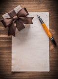 Penna stilografica della carta dell'arco di marrone di Giftbox sul bordo di legno d'annata Fotografia Stock Libera da Diritti