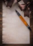 Penna stilografica della carta dell'arco legata scatole attuali sul bordo di legno Immagini Stock Libere da Diritti