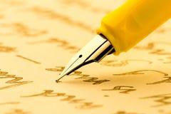 Penna stilografica gialla che scrive una lettera fotografie stock