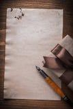 Penna stilografica legata della carta dell'arco del contenitore di regalo sul bordo di legno Immagine Stock