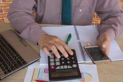 Penna sui conti di lavoro di ufficio con il computer di uso dell'uomo per conservare i dati nel fondo Concetto di contabilità Man Immagini Stock