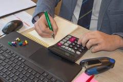 Penna sui conti di lavoro di ufficio con il computer di uso dell'uomo per conservare i dati nel fondo Equipaggi la mano con la pe Fotografia Stock Libera da Diritti