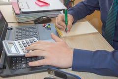 Penna sui conti di lavoro di ufficio con il computer di uso dell'uomo per conservare i dati nel fondo Equipaggi la mano con la pe Immagini Stock Libere da Diritti