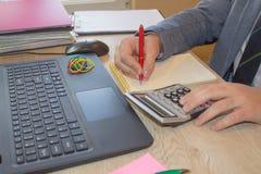 Penna sui conti di lavoro di ufficio con il computer di uso dell'uomo per conservare i dati nel fondo Equipaggi la mano con la pe Fotografia Stock