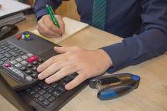 Penna sui conti di lavoro di ufficio con il computer di uso dell'uomo per conservare i dati nel fondo Equipaggi la mano con la pe Fotografie Stock