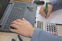 Penna sui conti di lavoro di ufficio con il computer di uso dell'uomo per conservare i dati nel fondo Equipaggi la mano con la pe Immagine Stock