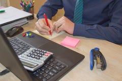 Penna sui conti di lavoro di ufficio con il computer di uso dell'uomo per conservare i dati nel fondo Equipaggi la mano con la pe Immagini Stock