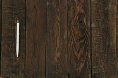 Penna sulla tavola di legno scura Vista superiore Immagine Stock