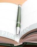 Penna verde che si trova sull'organizzatore aperto su uno scrittorio Fotografie Stock
