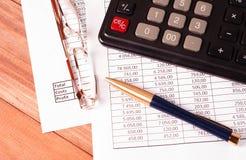 Penna, vetri e calcolatore sulle tavole di carta con i numeri Fotografia Stock