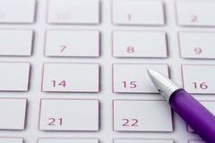Penna viola sul calendario 3 Immagini Stock