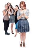 Pennalismflickor som använder smartphones royaltyfria bilder
