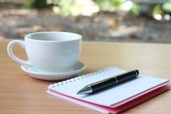 Pennan för kaffekoppen och anteckningsbokförläggas på en brun trätabell a royaltyfri fotografi