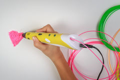 Pennan för printing för guling 3D för ungehandinnehavet med glödtrådar och gör hjärta på vit bakgrund Top beskådar Kopiera utrymm Royaltyfria Bilder