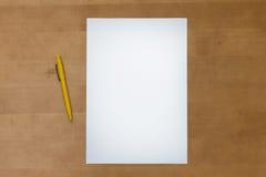 Pennan och tomt papper täcker på en trätabell Arkivbild