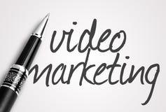 Pennan skriver den videopd marknadsföringen på papper Royaltyfri Fotografi