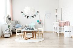 Pennant banner hanging over cradle. Fabric pennant banner hanging over a child`s white cradle standing next to a large armchair with a blue, cloud shaped pillow Royalty Free Stock Photo