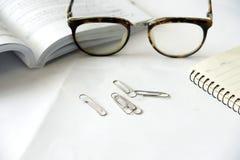 Pennanteckningsbok och glasögon Arkivfoto
