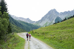 Pennaz Needles. LA BALME, FRANCE - AUGUST 25: Mont Blanc tour hikers on countryside road, with Pennaz Needles in the background. The tour crosses France, Italy Royalty Free Stock Photo