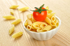 Penne意大利面食和在一个小的碗的一个蕃茄 免版税库存照片