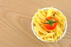 Penne意大利面食和在一个小的碗的一个蕃茄 免版税图库摄影