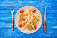 penne面团用蕃茄和芝麻菜 免版税库存图片