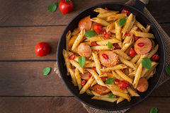 Penne面团用西红柿酱用香肠,蕃茄,在煎锅装饰的绿色蓬蒿 免版税库存照片