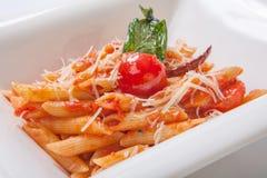 Penne面团用西红柿酱洒与在一块深白色板材的帕尔马干酪 库存照片