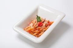 Penne面团用西红柿酱洒与在一块深白色板材的帕尔马干酪 免版税图库摄影