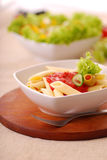 Penne. Delicious penne with tomato sauce on a wooden plate Royalty Free Stock Photos