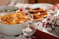 Penne alla Arabiata. Table served with italian food - penne, pizzas royalty free stock image