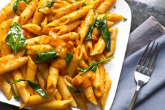 Penne Alla Vodka. Penne pasta in creamy vodka tomato sauce with sauteed baby spinach leaves Royalty Free Stock Images