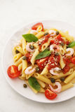 Penne alla vodka pasta. In tomato sauce with shrimp and capers on a white plate Stock Photography