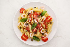 Penne alla vodka pasta. In tomato sauce with shrimp and capers on a white plate Royalty Free Stock Photo