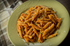 Penne Alla Vodka. In rustic kitchen setting on green plate Royalty Free Stock Image