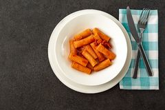 Penne Amatriciana fresh pasta with parmesan cheese on dark backg royalty free stock photography