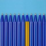 Penne blu ed una differenti su fondo blu Concetto di individualità Fotografia Stock
