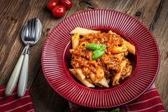 Penne bolognese στο κόκκινο πιάτο Στοκ φωτογραφίες με δικαίωμα ελεύθερης χρήσης