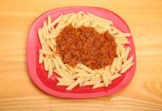Penne Bolognese sul piatto rosso Fotografia Stock