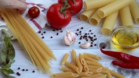 Penne, cannelloni, spaghetti with ingredients for cooking pasta. Ingredients for cooking pasta. Different kinds of pasta: penne, cannelloni, spaghetti stock video