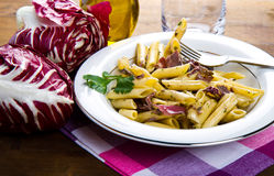 Penne  with chicory and bacon Stock Photos