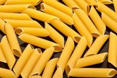 Penne closeup. Italian pasta (penne) on black background macro stock photos