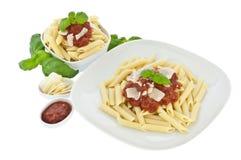 Penne in der Schüssel und auf einer Platte mit tomatoe Soße Stockfoto
