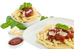Penne in der Schüssel und auf einer Platte mit tomatoe Soße Stockbild