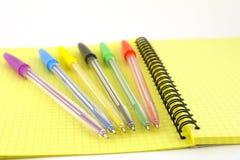 Penne di colore sul scrittura-libro giallo Fotografie Stock Libere da Diritti