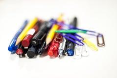 Penne e matite nel fondo bianco Fotografia Stock