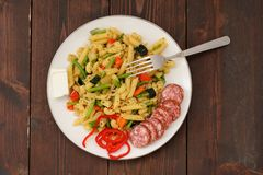 Penne with green beans, red hot pepper, salami and feta cheese w Stock Photo