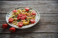 Penne makaron w pomidorowym kumberlandzie z kurczakiem, pomidory dekorował pietruszki Obraz Royalty Free