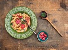 Penne makaron z tuńczyków pomidorami w zieleń talerzu i kumberlandem fotografia royalty free