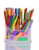 Penne, matite ed eraser luminosi in supporto Fotografie Stock